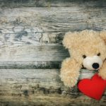 oso de peluche alcanzando un corazon rojo